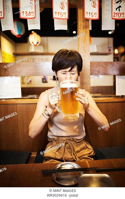 Woman sitting at a table in a restaurant, drinking from large glass of beer
