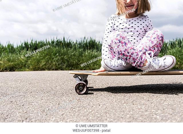 Girl on skateboard on country lane