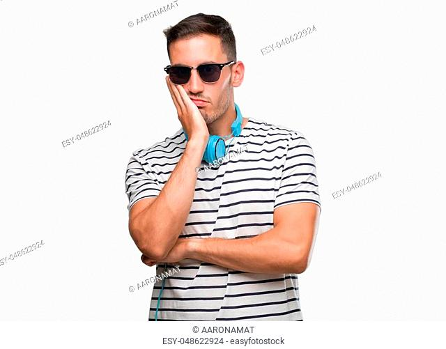 Handsome young man wearing headphones thinking looking tired and bored with depression problems with crossed arms