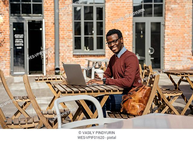 Young man using laptop in a coffee shop, drinking coffee