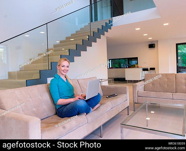 Young woman using her laptop computer in her luxury modern home, smiling