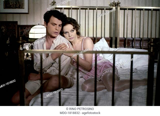 Italian actress Laura Antonelli and Italian actor and director Michele Placido hugging sitting together on a double bed in the film The Divine Nymph