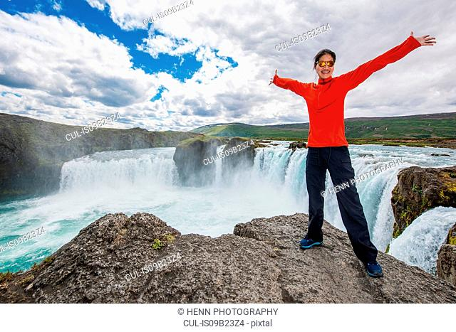 Woman standing in front of waterfall, arms raised, Godafoss, Myvatn, Iceland