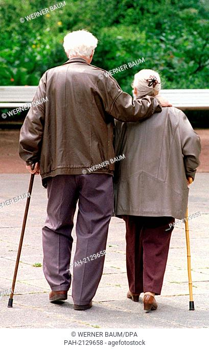 Old man lovingly embraces his partner while going for a stroll in a Saarbrücken parkway, pictured on 2nd Juli 1997. | usage worldwide