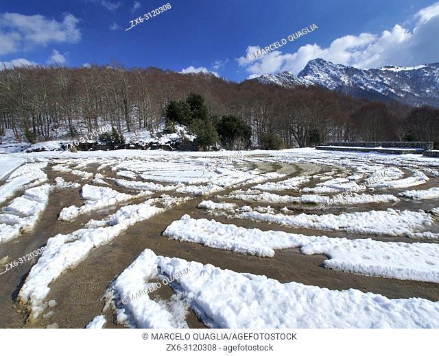 Snow trails at Ferreries Area parking lot. Les Agudes Peak at background. Montseny Natural Park. Barcelona province, Catalonia, Spain