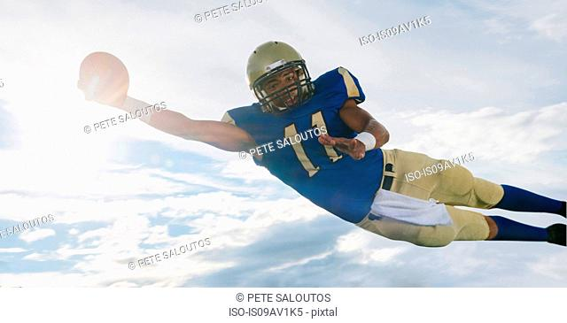 Male teenage American football player catching ball mid air against sunlit sky