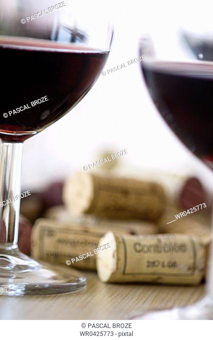 Close-up of glasses of red wine and corks