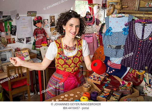 Button maker in colorful dirndl with Collier button trimmings in handicraft studio working with red yarn and utensils for Posamentenknöpfe