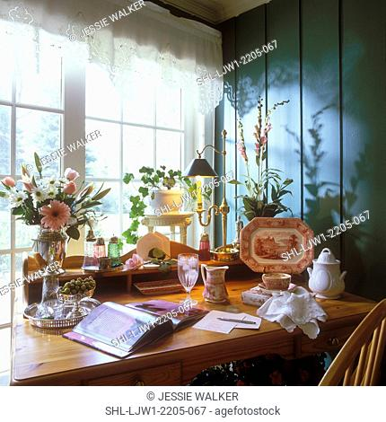 COLLECTION - Desk with display of antique dishes silver topped shaker, dark green wall, lace valance, writing desk, feminine