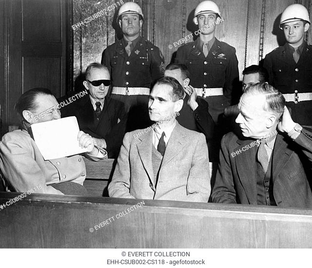 Nazi defendants under guard in the dock at Nuremberg War Crimes Trial, Feb. 5, 1946. L-R: Herman Goering covers his grin with a piece of paper; Adm