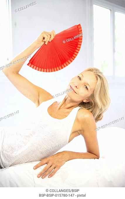 Woman cooling down with a fan