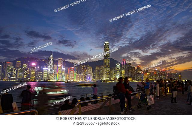 The famous Tsim Sha Tsui promenade, and tourists enjoying the evening view of Hong Kong Island, Hong Kong, China
