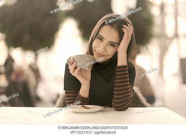 portrait of coy woman holding coffee cup while enjoying break at table in café, in Munich, Germany