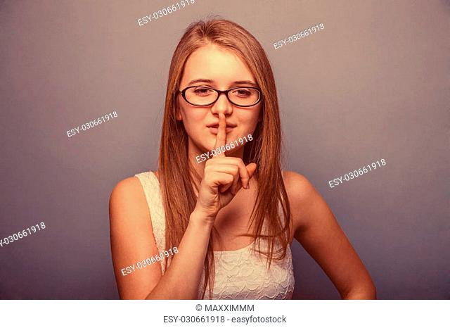 woman in a white dress with glasses shows a sign quietly retro