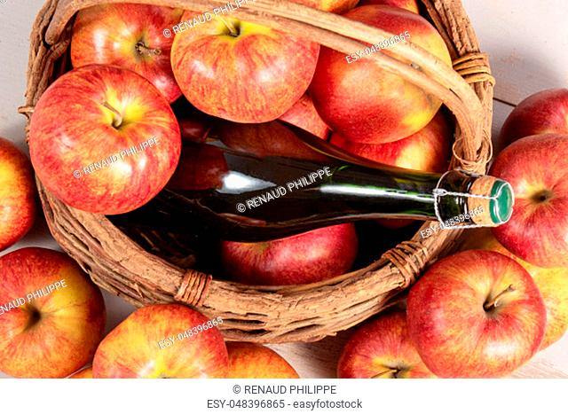 bottle of cider and delicious apples in basket