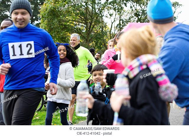Spectators offering water to runners at charity run in park