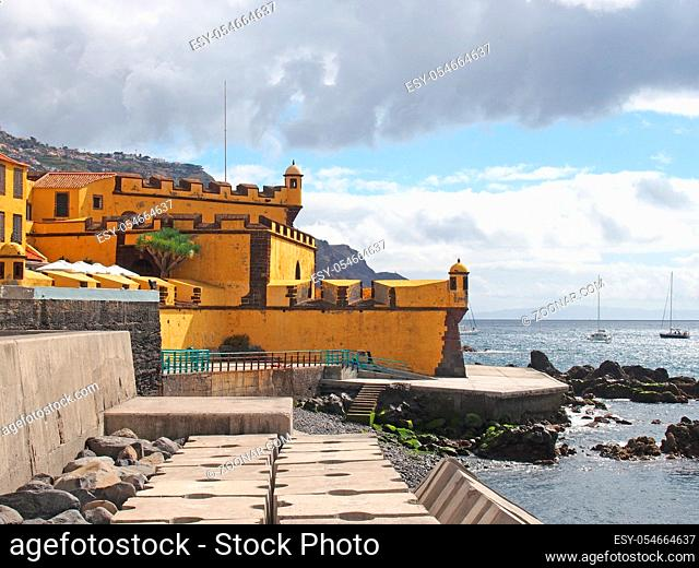 view of the 17th century yellow fort Fort of São Tiago in funchal madeira taken from the seafront with sunlit blue sea and boats with the hills surrounding the...