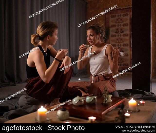 Women drinking tea and talking during ceremony
