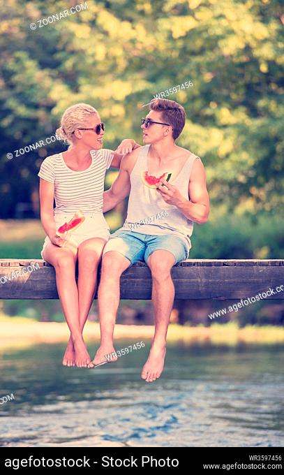 couple in love enjoying watermelon while sitting on the wooden bridge over the river in beautiful nature