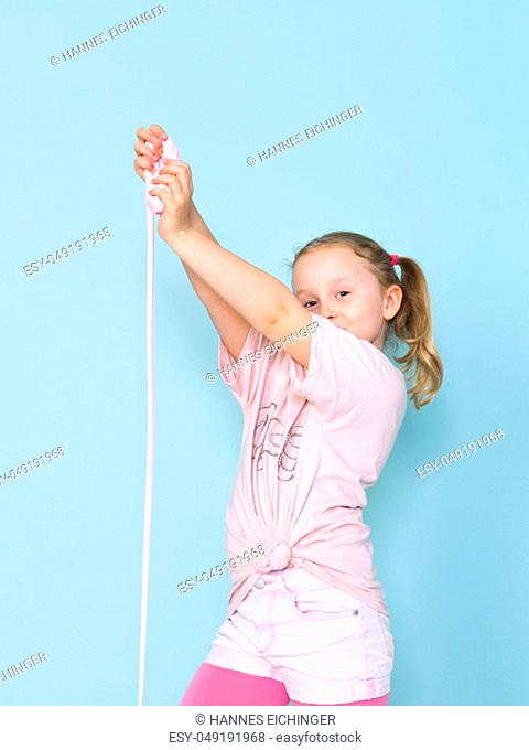 beautiful 8 year old girl is playing with pink slime in front of blue background