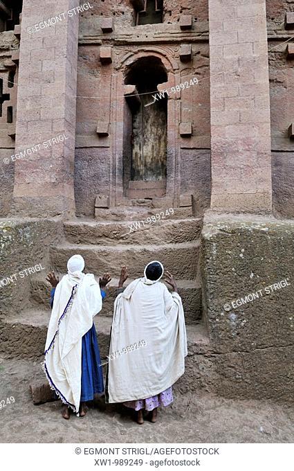 ethiopian orthodox woman praying in front of a church in Lalibela, Amhara, Ethiopia, Africa