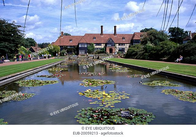 Wisley Royal Horticultural Society Garden. View across formal pond with water lilies towards the Tudor style half timbered main entrance building
