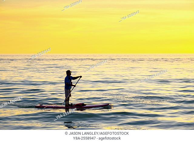 A man on a stand-up-paddleboard (SUP) at sunset, Boracay Island, Aklan Province, Western Visayas, Philippines
