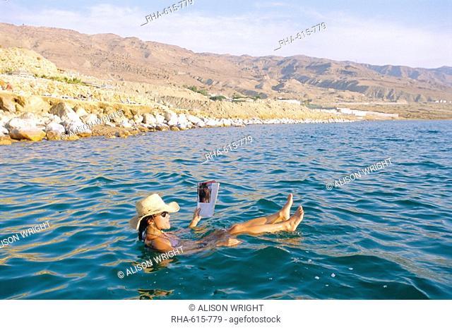 Woman floating in the Dead Sea reading a magazine, Aqaba, Jordan