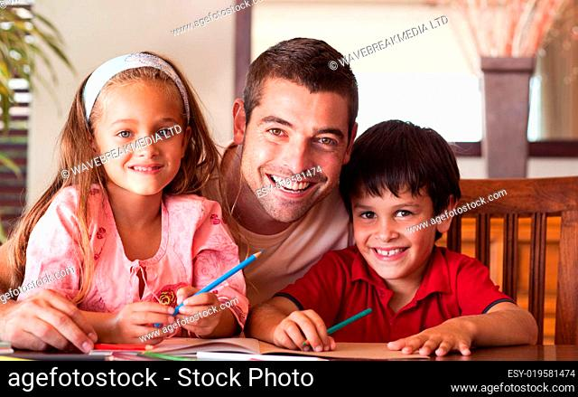 Smiling father helping his children for homework