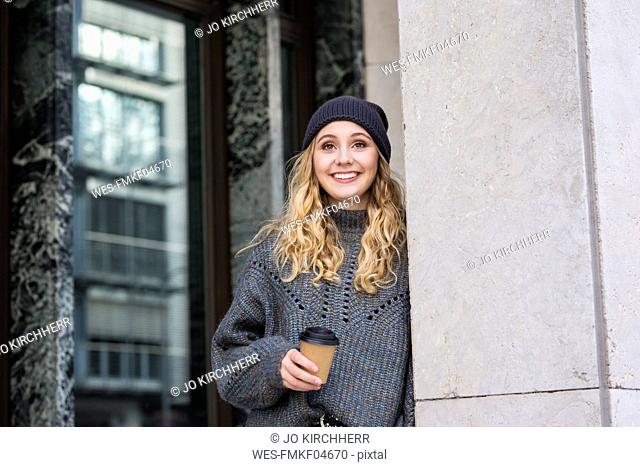 Portrait of fashionable young woman with coffee to go in autumn