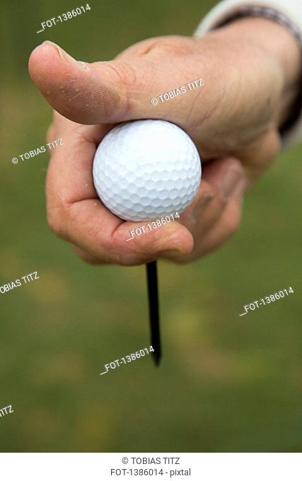 Cropped image of hand holding golf ball outdoors
