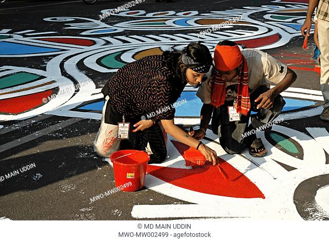 Students of the Institute of Fine Arts paint alpona color designs on the road in front of Shahid Minar Martyr's Monument 8 hours before the occasion of the...