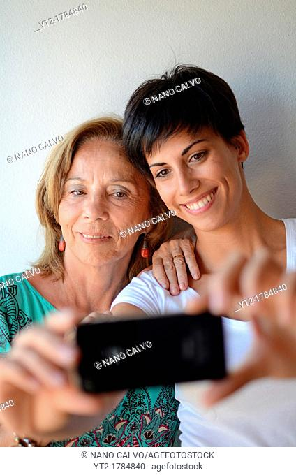 Mother and daughter take a self portrait with mobile telephone