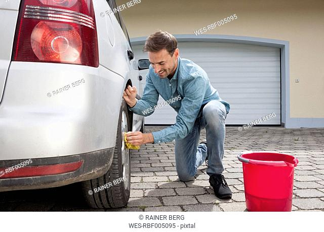 Man cleaning car on driveway of a house