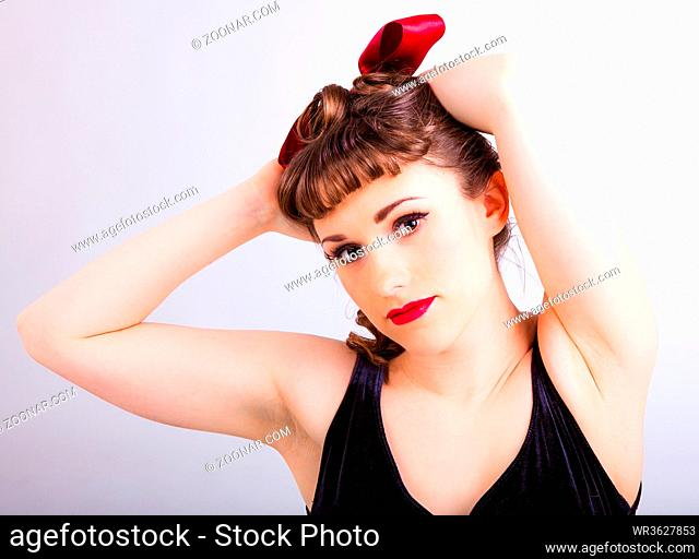 young girl in fifties pin-up style with a red hair ribbon