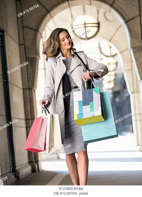 Businesswoman with shopping bags checking wristwatch in cloister