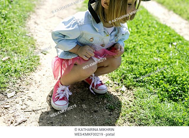 Little girl crouching on a meadow searching something