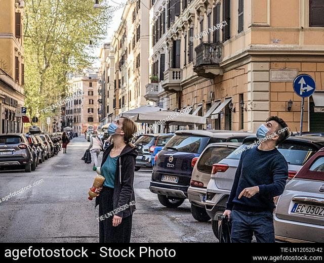 Two young men with protective masks exchange small talk with some friends at the window along the streets of Testaccio during the Coronavirus emergency in Rome