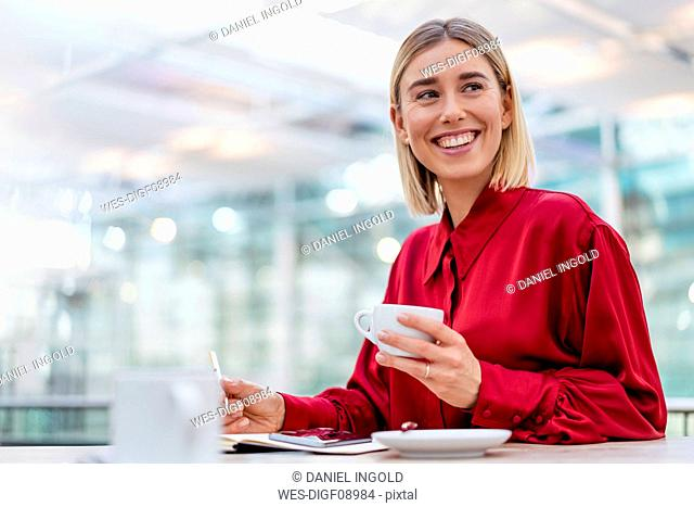 Happy young businesswoman taking notes in a cafe