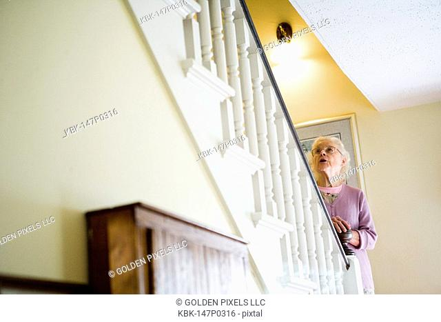 Senior woman standing by staircase alone, looking up the stairs