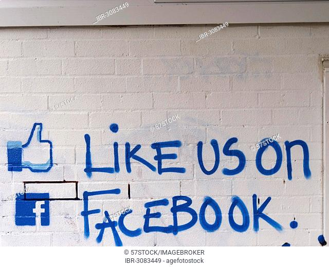 Like us on facebook call to action painted on a brick wall, United Kingdom