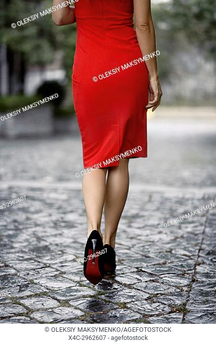 Sexy woman in an elegant red dress walking away on a wet cobbled city street closeup of legs in high heel shoes