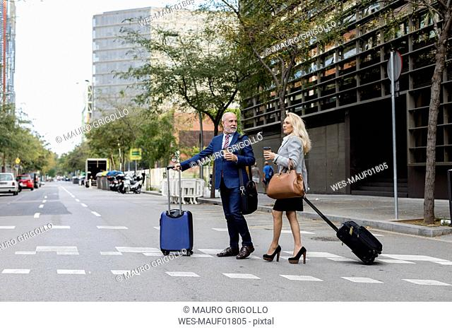 Senior businessman and businesswoman with baggage crossing the street in the city