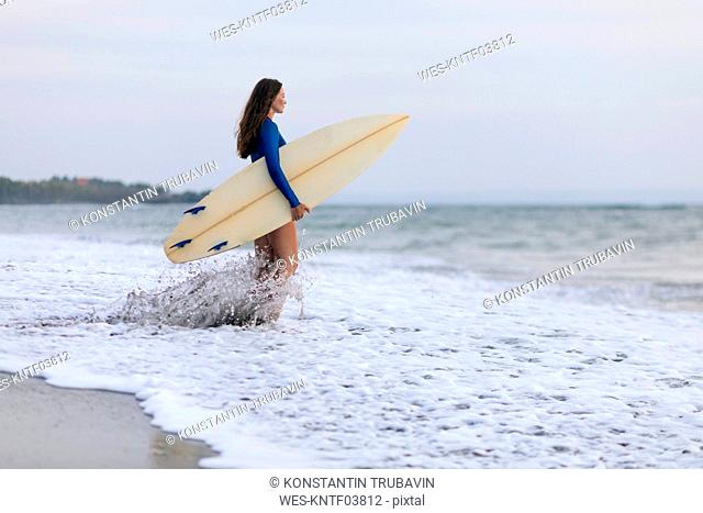 Young woman with surfboard at the beach, Kedungu beach, Bali, Indonesia