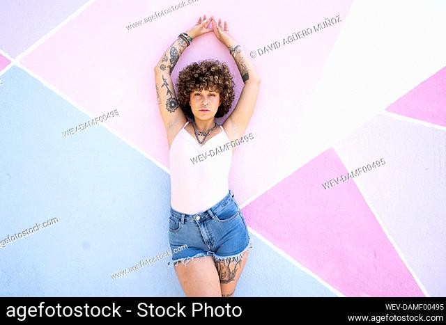 Woman with hand raised standing against multi colored wall