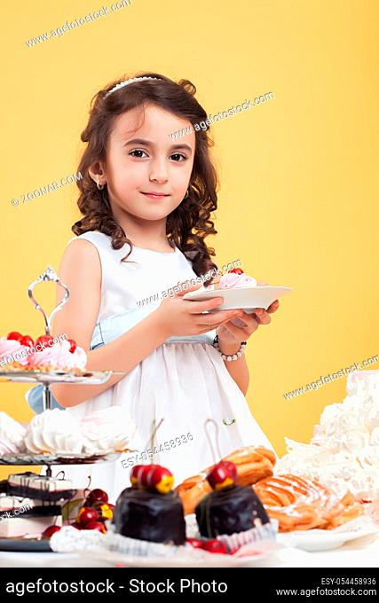 Adorable little brown-eyed model posing with sweets