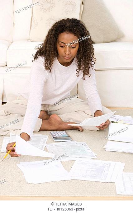 Woman paying bills on floor