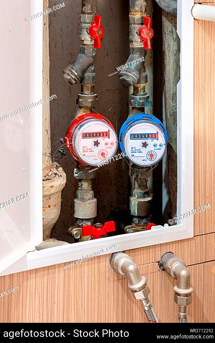 Sealed counters for metering consumption. Hot and cold water meters on pipes with red taps