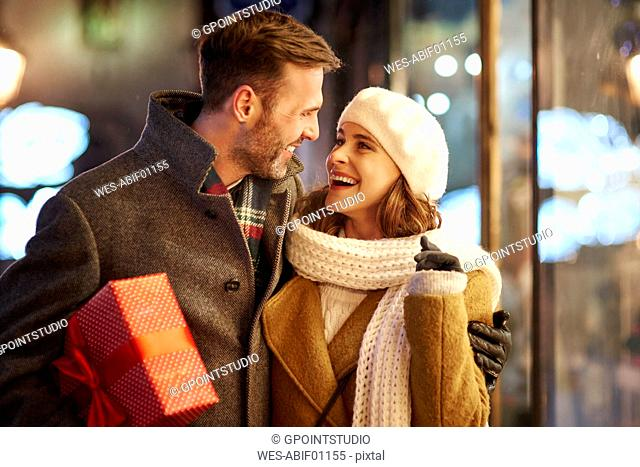 Happy couple on shopping tour at Christmas time looking at each other