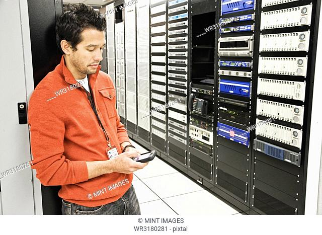 Caucasian male technician on a cell phone in a large computer server room
